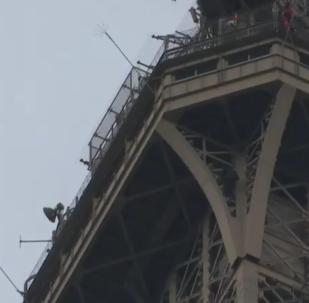 Neznámý muž leze po Eiffelově věži