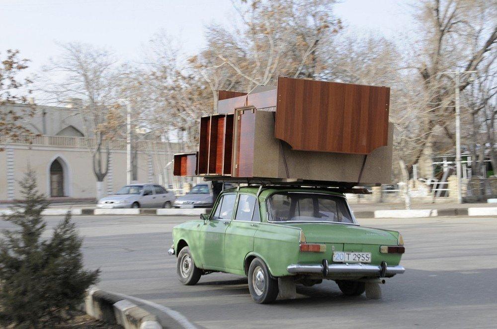 Zelený Moskvič jede po ulici v Buchaře, Uzbekistán.