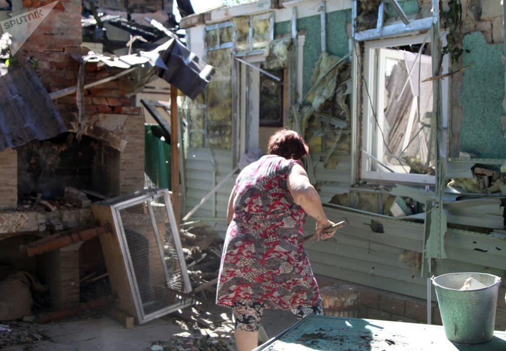 Žena uklízí vedle domu v Doněcku po ostřelování.