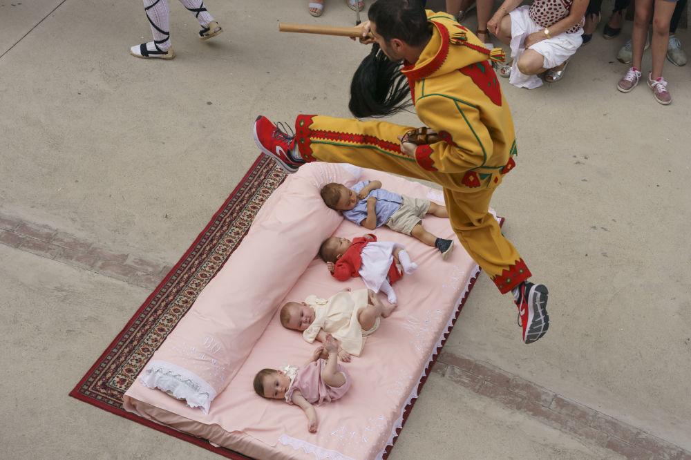 Muž v obleku ďábla skáče přes novorozence během každoročního festivalu El Colacho ve Španělsku.