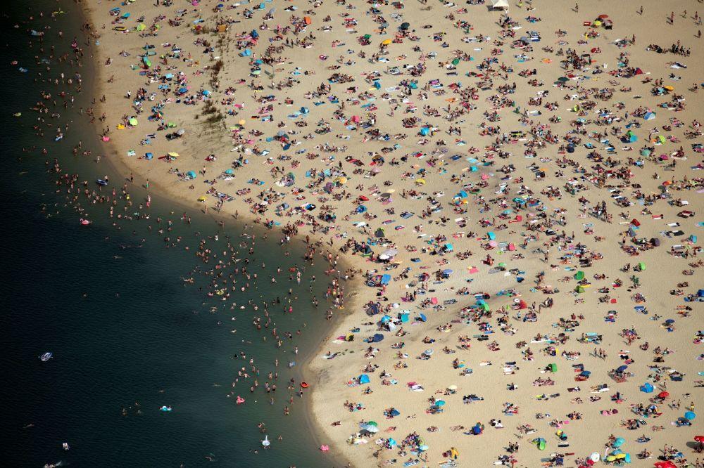 Lidé odpočívají na pláži za horkého počasí v Německu.