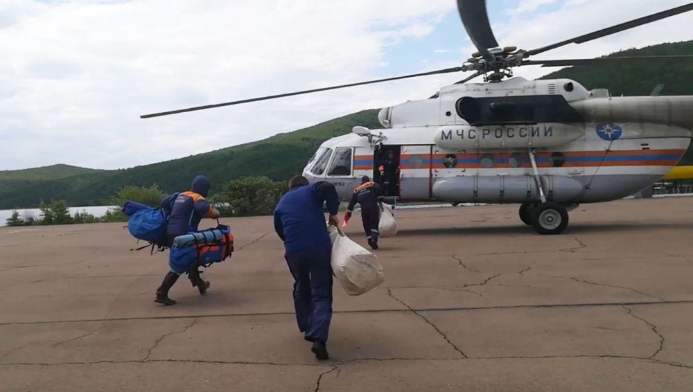 Záchranáři míří k vrtulníku pro oblet kolem zaplavených oblastí v Irkutské oblasti.