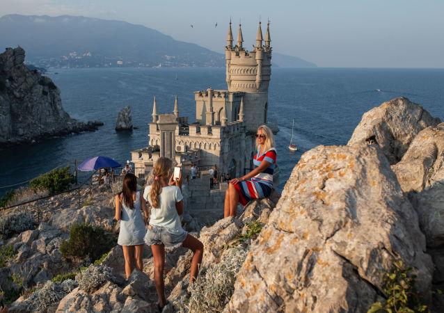 Turisté se fotí u Vlaštovčího hnízda na Krymu.
