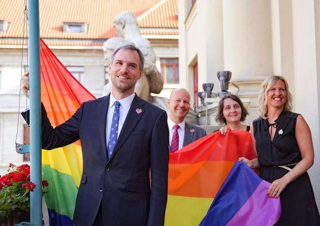Český politik Zdeněk Hřib na pozadí duhové vlajky v Praze