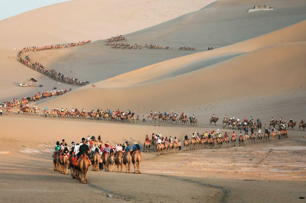 Turisté na velbloudech v poušti v Dunhuangu, Čína.