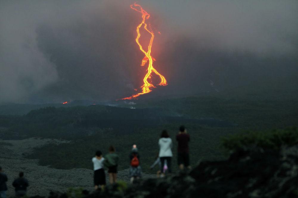 Lidé sledují erupci sopky Piton de la Furnes na ostrově Réunion, Francie.