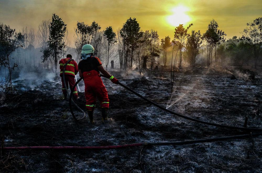 Hašení lesních požárů v Sumatře, Indonésie.
