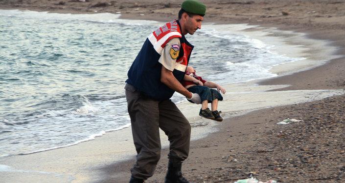 Turecký policista nese tělo utonulého chlapce