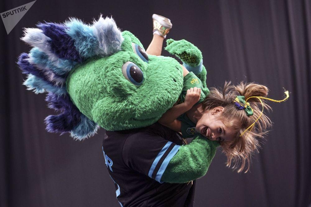 Maskot 37. mistrovství světa v moderní gymnastice 2019 Gur-Gur si hraje s malou dívkou.