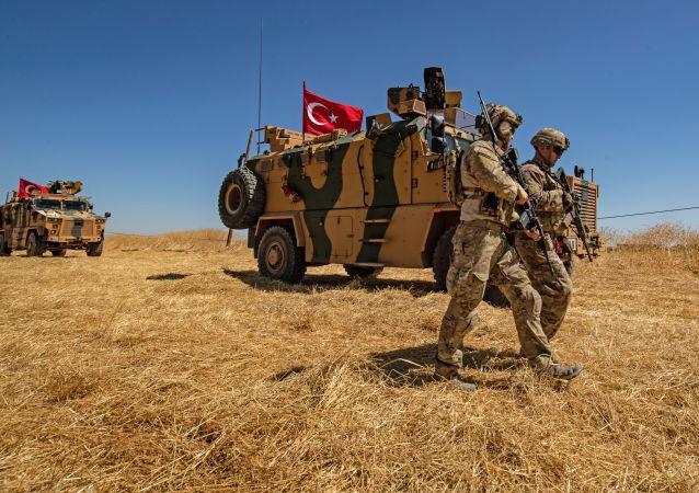 Američtí vojáci prochází okolo tureckého obrněného vozidla v okolí města Tell Abiad