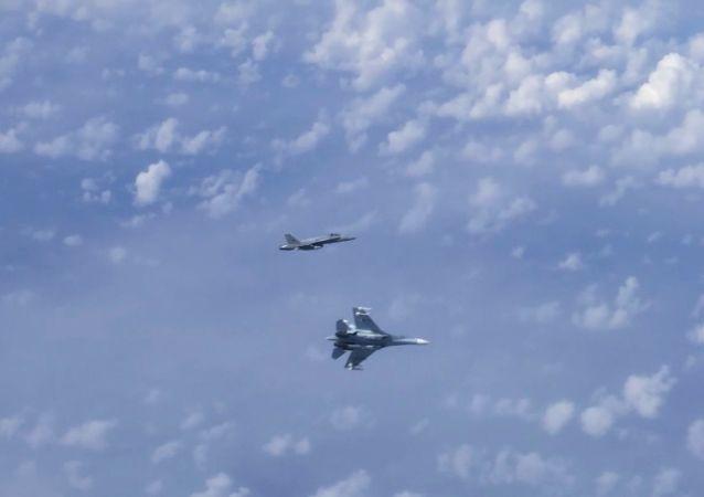 Letoun Su-27 vytlačuje stíhačku NATO F-18, která se přiblížila k letadlu ruského ministra obrany Sergeje Šojgu nad neutrálními vodami Baltského moře