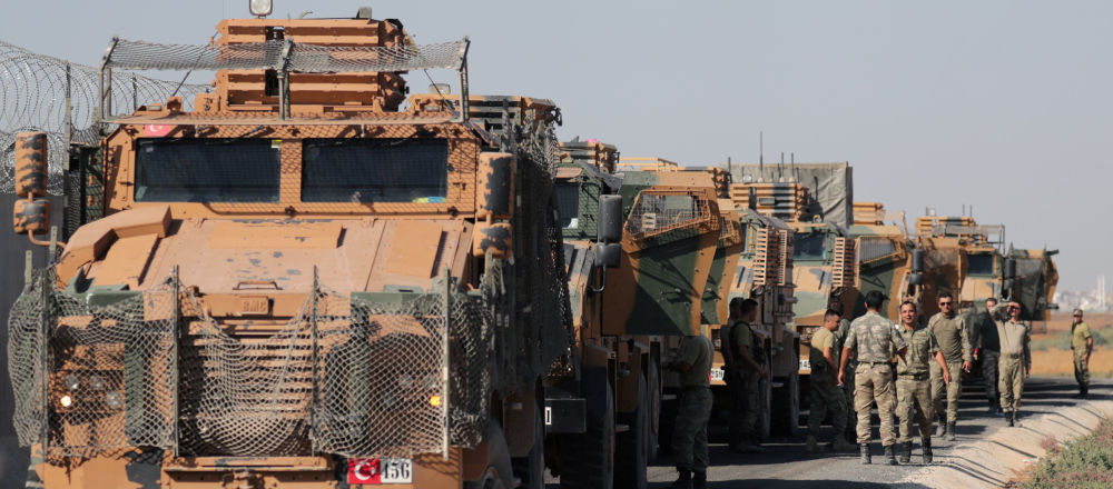 Turečtí vojáci stojí poblíž vojenských náklaďáků ve vesnici Yabisa, poblíž turecko-syrských hranic