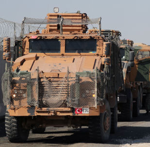 Turkish soldiers stand near military trucks in the village of Yabisa, near the Turkish-Syrian border, Syria, October 12, 2019. REUTERS/Khalil Ashawi