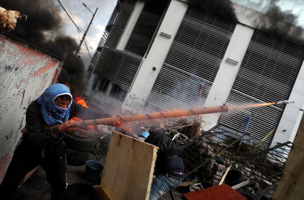 Demonstrant střílí ze zbraně vlastní výroby během protestů v ekvádorském Quito.