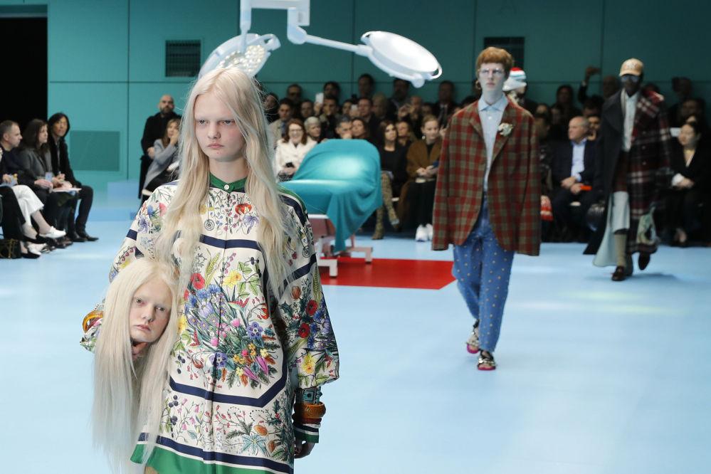 Modelka s falešnou hlavou v náručí předvádí kolekci Gucci podzim-zima 2018-2019 na týdnu módy v Miláně.