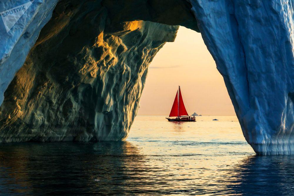 Jachta Petr I. pluje kolem ledovce v grónských vodách v rámci expedice ruské společnosti Rusark.