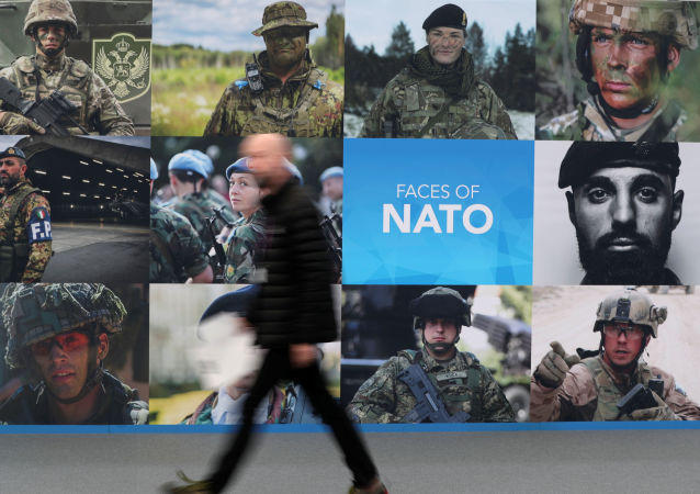 A man walks past a NATO sign ahead of a NATO leaders summit at the Grove in Watford, Britain December 3, 2019