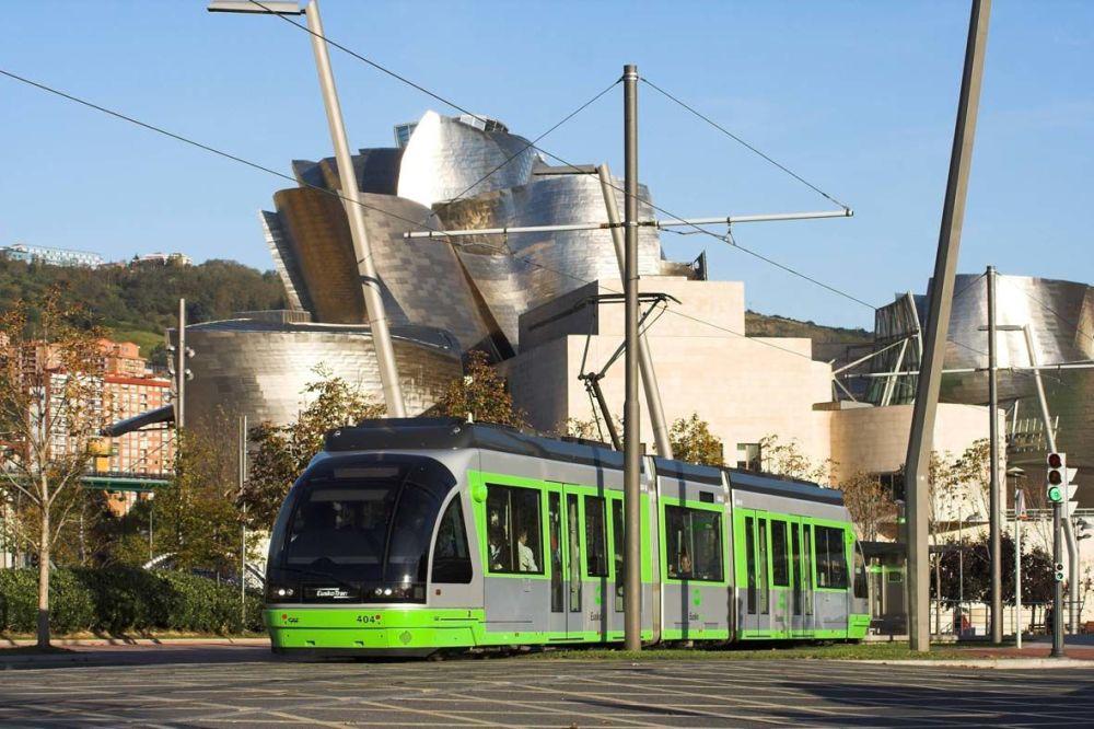 Sytě zelená tramvaj na pozadí Guggenheimova muzea v Bilbau, Španělsko