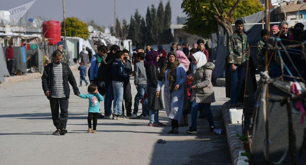 Lidé v uprchlickém táboře poblíž Damašku