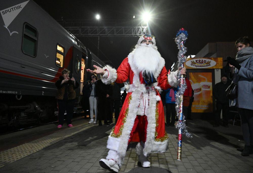 Muž v kostýmu Děda Mráze u vlaku