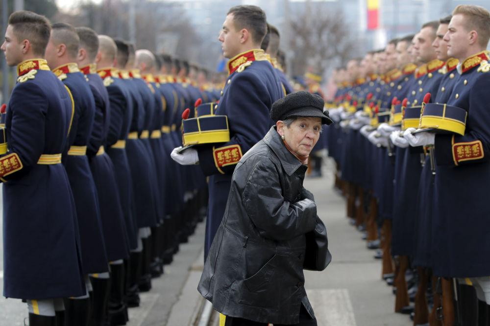 Žena míjí čestnou stráž na Hřbitově hrdinů během 30. výročí protikomunistického povstání v Rumunsku