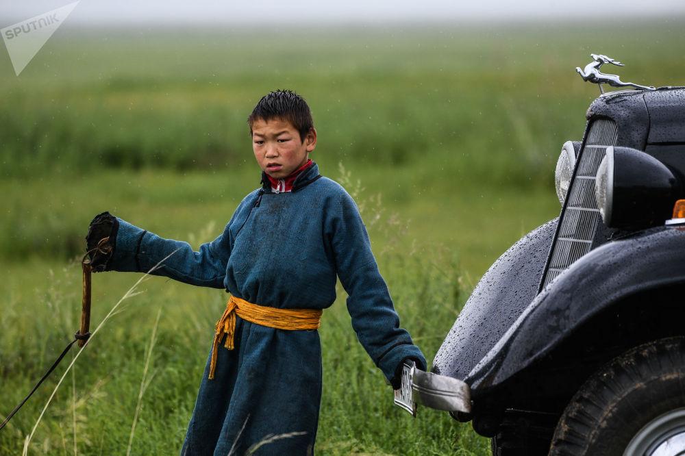Chlapec vedle automobilu GAZ-M1 na poli, Mongolsko