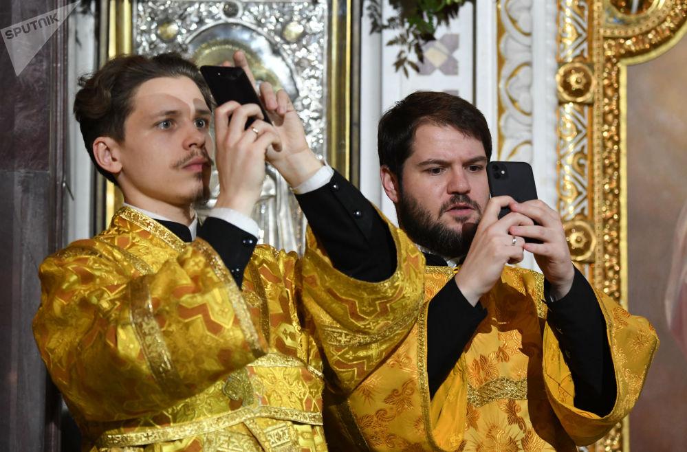 Pravoslavní věřící fotografují během vánoční bohoslužby v katedrále Krista Spasitele v Moskvě