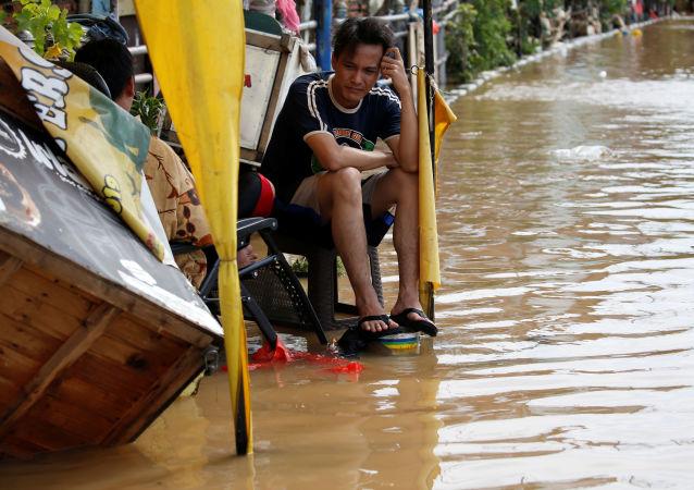 Muž sedí u zatopeného domu v Jakartě
