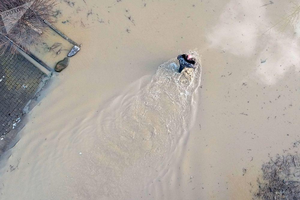 Muž uprostřed zaplavené ulice