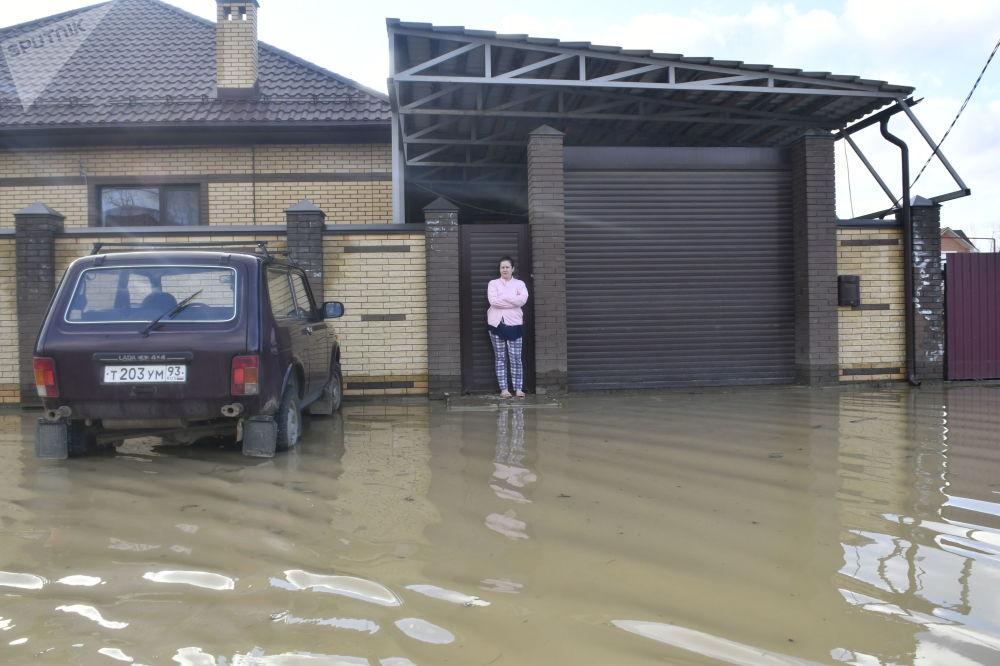 Žena vedle brány vlastního domu ve městě Gorjačij Ključ Krasnodarského kraje