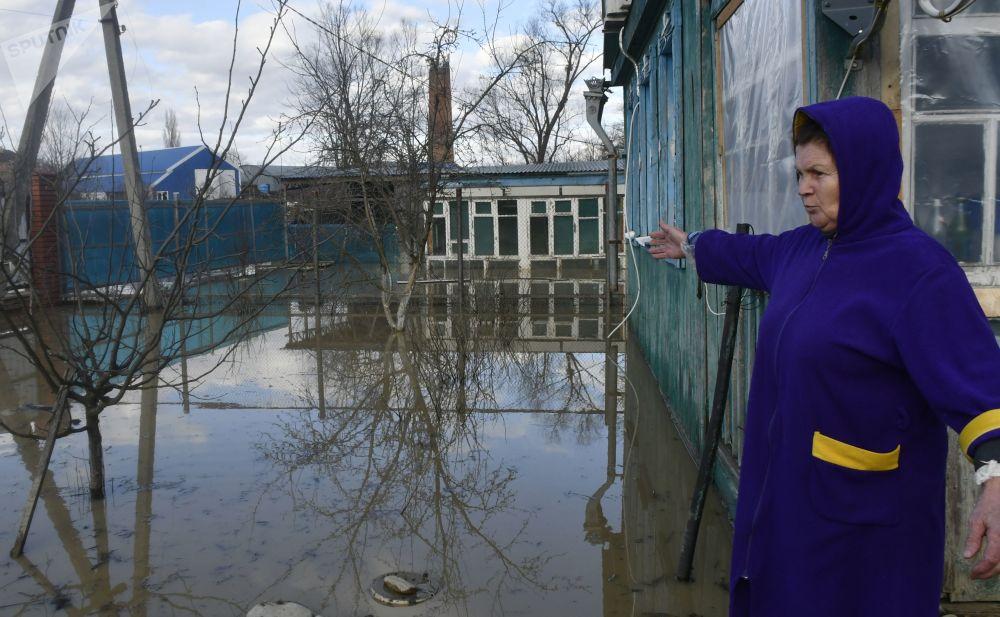 Žena na dvoře u svého rodinného domu