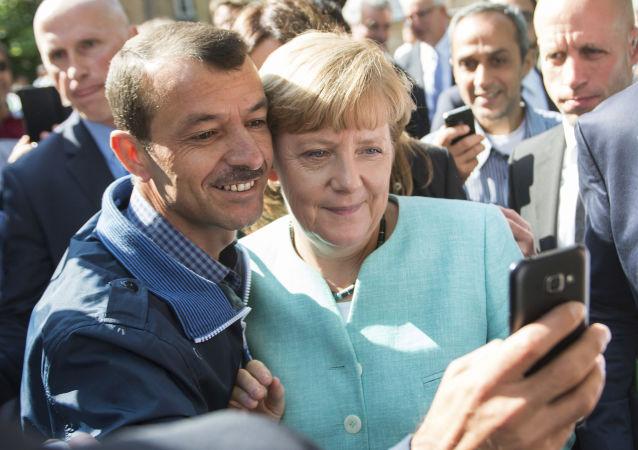 Uprchlík se fotí s německou kancléřekou Angelou Merkelovou