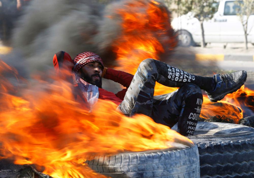 Demonstrant v Iráku sedí mezi hořícími pneumatikami, které blokují cestu během protivládních protestů v Nadžafu