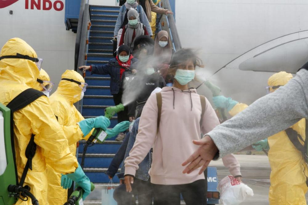 Lékaři stříkají indonéské občance antiseptikem po příletu z čínského Wu-chanu