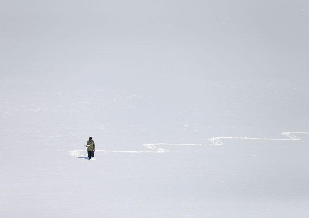 Muž na zasněženém jezeře Qargha v Kábulu, Afghánistán.