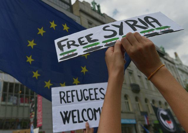 Lidé s bannery běženci vítejte s Svobodná Sýrie během demonstrace na podporu příchodu běženců do Evropy v Praze