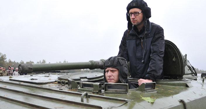 Ukrajinský premiér Arsenij Jaceňuk jede na obrněném transportéru