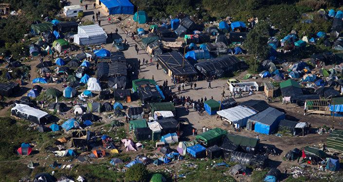 Migranti v táboře New Jungle v Calais, Francie