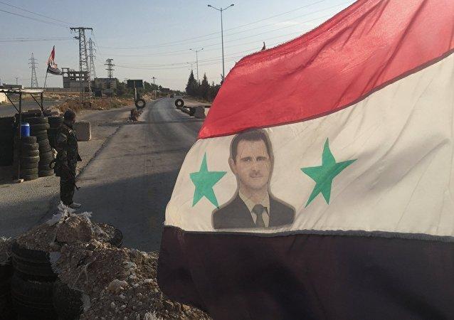 Sýrská vlajka s fotografii Bašára Asada