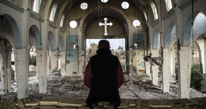 Syřan se modlí v chrámu, který byl zničen Daiš