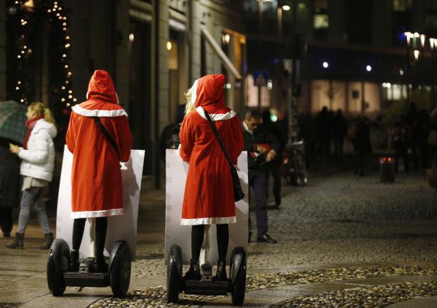 Dívky v kostýmech Santa Clause na segwayích v Milánu