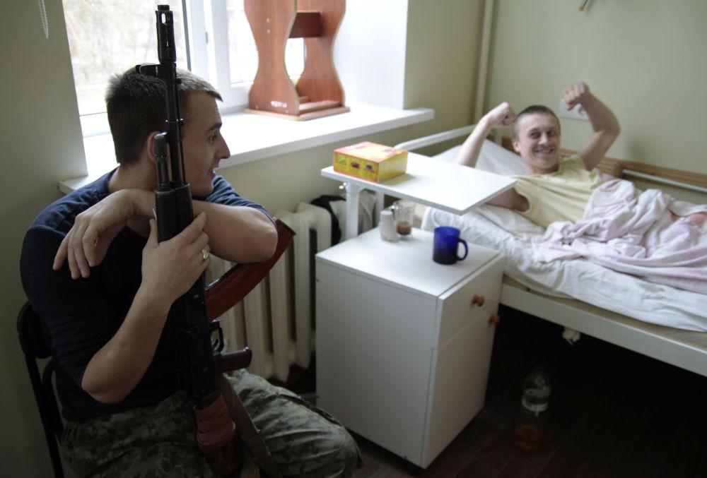 Zraněný ukrajinský voják a domobranec, který ho hlídá, v nemocnici v Doněcku
