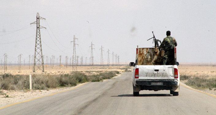 Syrští vojáci vedle syrského města Rakka