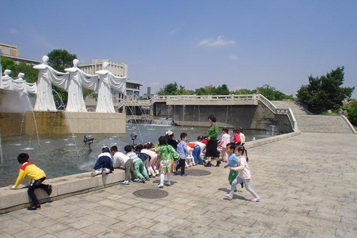 Děti si hrají u fontány