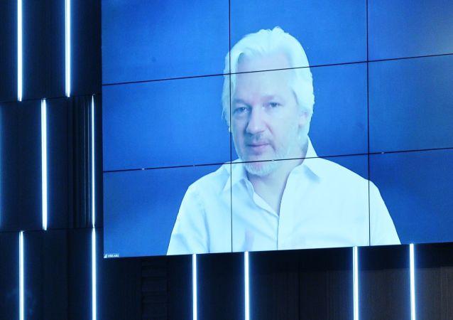Julian Assange během videorozhovoru na mezinárodním mediálním fóru MIA Rossia Segodnia Nová epocha žurnalistiky: loučení s mainstreamem