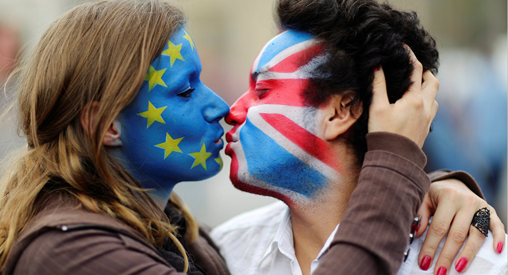 Muž a žena s tvářemi v barvách vlajek EU a Velké Británie