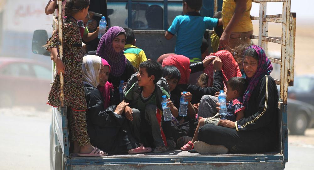Irácké ženy s dětmi na cestě do běženeckého táboru