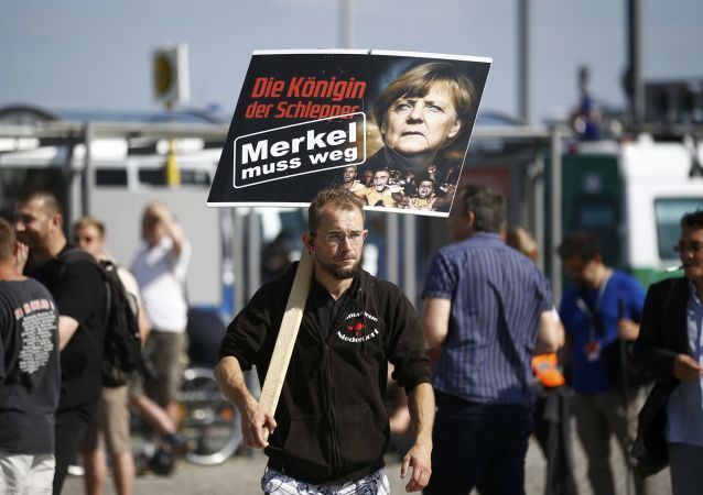 Muž s plakátem Merkelová musí odejít