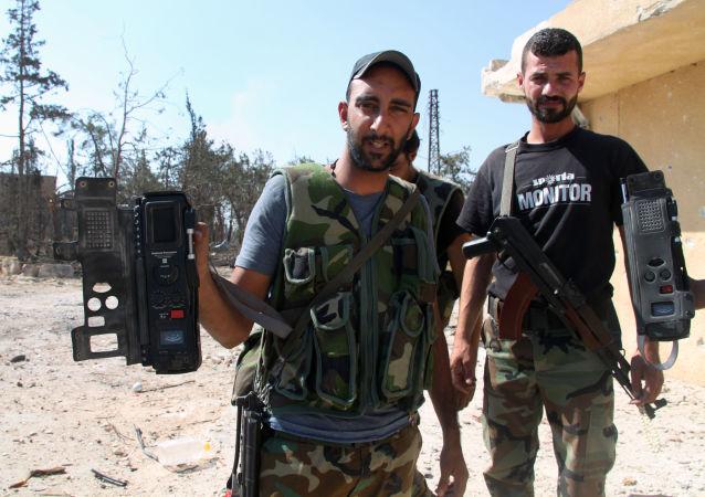 Syrští vojáci ukazují komunikační prostředky, které našli po teroristech