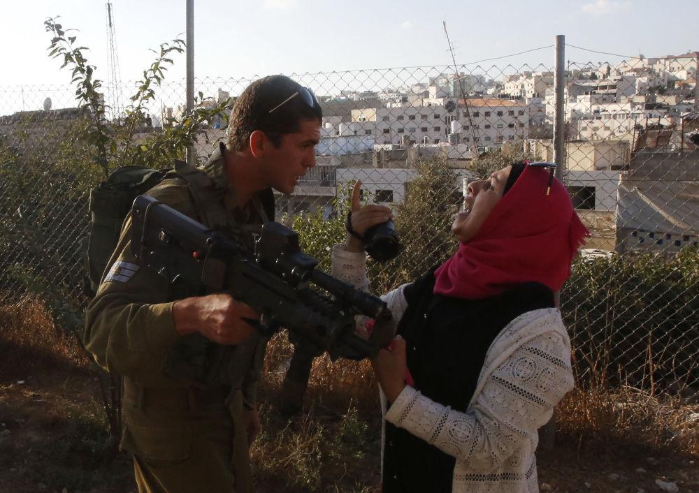 Voják izraelské armády se pře s Palestinkou, která se pokouší natočit útok na vojáky v Hebronu